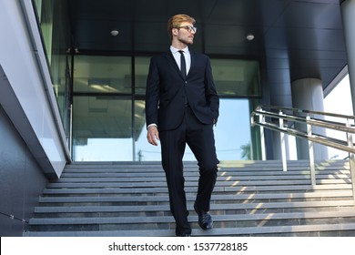 Successful young businessman walking down the stairs outside the office building.