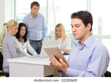 Successful young businessman working on tablet