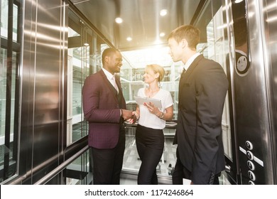 successful and young businessmen in the elevator business center rides to work