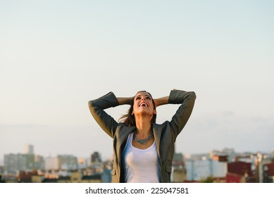 Successful young businesswoman after business or job achievement towards city background. Professional joyful woman outside.