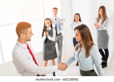 Successful young businesswoman and businessman shaking hands over a deal in front their business team with hands raised celebrating.