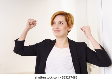 Successful young businesswoman celebrating raising her clenched fists in the air with a happy smile of satisfaction