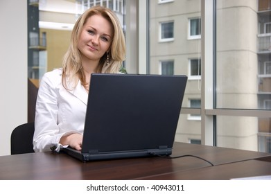 Successful young businesswoman with laptop computer in the office