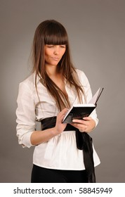 Successful young businesswoman with notebook, studio shot.