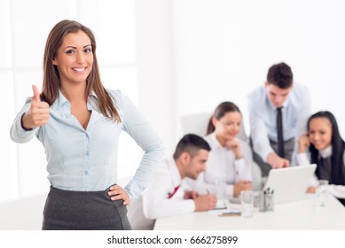 Successful young businesswoman standing proudly in the office and looking at the camera. Her young colleagues working at laptop on desk.