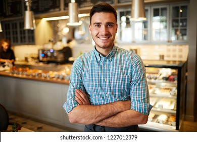 Successful young cafeteria staff or its owner crossing his arms on chest and looking at you