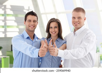 Successful young caucasian casual startup business team giving thumbs up at financial center. Smiling, standing, looking at camera.