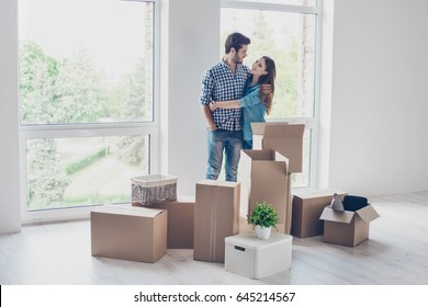 Successful young couple is moving to new nice place and embracing, around are carton boxes with their belongings. The room is very light and bright, they are wearing casual outfit