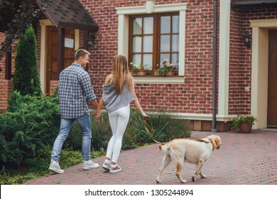 Successful young couple walking with a dog near home. Beautiful family moving to their new house.