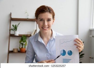 Successful young executive manager making video conference call share financial report shown in charts and diagrams with client smiling looking at camera. Coaching online training and vlogging concept