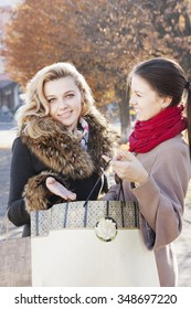 Successful young girlfriends with shopping outdoors