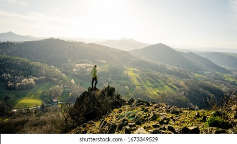 Successful young hiker standing on the top of the mountain and looking around.