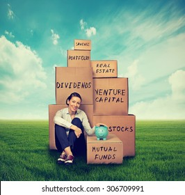 Successful young investor. Woman with piggy bank and boxes sitting outdoors on green grass