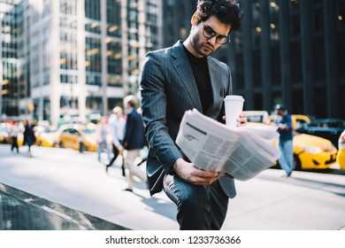 Successful young male economist searching article with financial news in morning newspaper holding tasty coffee to go in hand.Pensive manager iin formal wear reading business press in urban setting