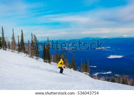 Successful young man skiing in the mountains Sheregesh. Caucasian Skier on a background of sky. A skier dressed in a bright costume descends from the mountain on skis at high speed.