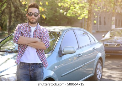 Successful young man standing near car