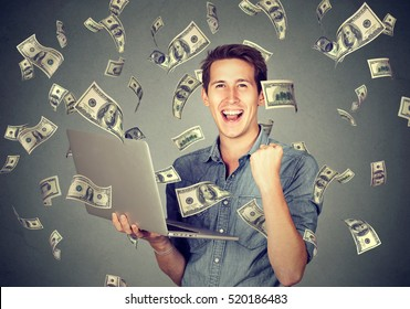 Successful young man using laptop building online business making money dollar bills cash falling down. Money rain. Beginner IT entrepreneur success economy concept