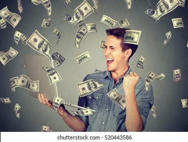 Successful young man using laptop building online business making money dollar bills cash falling down. Money rain. Beginner IT entrepreneur success economy concept