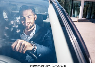 Successful young man wearing checkered shirt and jacket seating in black car near the office