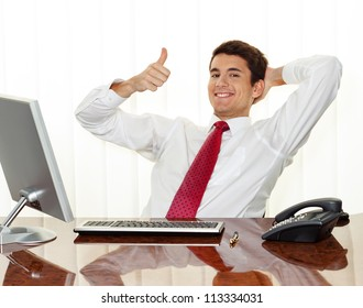a successful young manager sitting at desk, smiling.