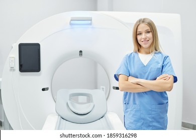 Successful young pretty doctor in blue uniform crossing arms by chest while standing in front of camera against ultra sound machine