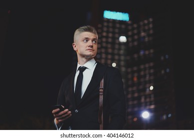Successful young professional businessman with smartphone in black suit at night near his office