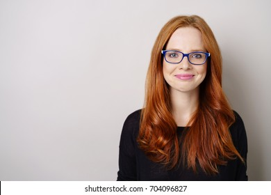 Successful young red head woman wearing glasses looking at the camera with a beaming smile of pleasure over white with copy space