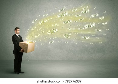 Successful young sales person making a lot of money concept illustrated with euro dollar bills flying out of a box held in his hand.