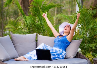 Successful young woman in dress and white hat using laptop rejoicing the success of the project using a computer, outdoor near swimming pool. Summer vacation day, freelance, working outdoor