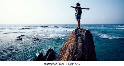 Successful young woman hiker outstretched arms on seaside rock cliff edge