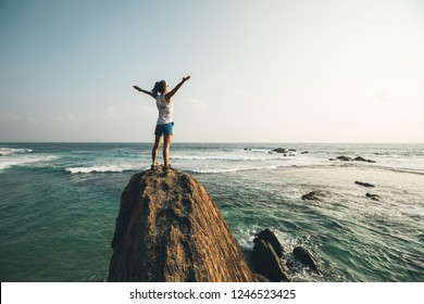 Successful young woman outstretched arms on seaside rock cliff edge