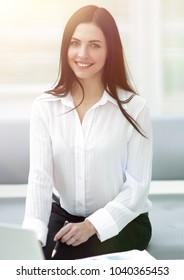 successful young woman sitting at a desk on a blurred background