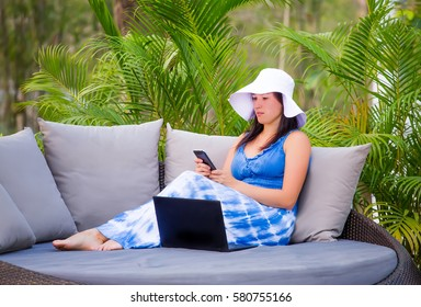 Successful young woman using laptop rejoicing the success of the project using a computer and a mobile phone. Summer vacation day, freelance, communication in internet