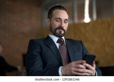 A successfull businessman reading a text message on a cellphone while sitting in his office.He is smiling while reading. He is wearing a black suit and a tie. He has a mustache and a beard.He is