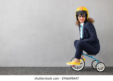 Successfull businesswoman driving toy car outdoor. Funny young woman against concrete wall background. Business srart up and winner concept