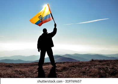 successfull silhouette man winner waving Ecuador flag on top of the mountain peak