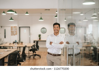 Successfull young Asian businessman smiling confidently while leaning against a glass wall with his arms crossed in a large modern office
