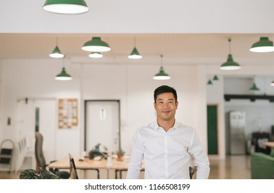 Successfull young Asian businessman smiling confidently while standing alone by desks in a large modern office