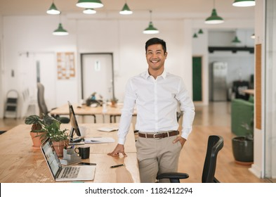 Successfull young Asian businessman smiling confidently while standing alone by his desk in a large modern office