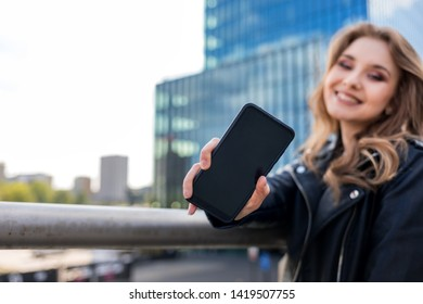 Successfull young businesswoman showing copyspace blank screen of smartphone with modern office building in background