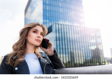 Successfull young businesswoman talking on phone with modern office buildings in the background