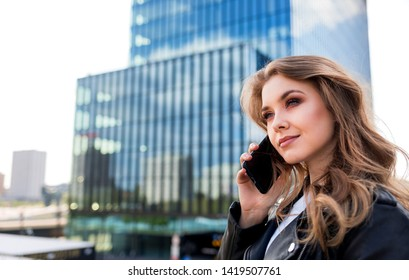 Successfull young businesswoman using smartphone with modern office buildings in the background