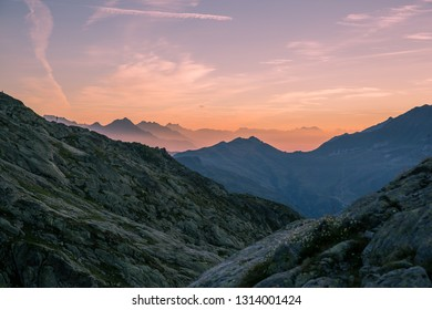 Succession of Alpine Mountains at Dawn with a Crimson Sky