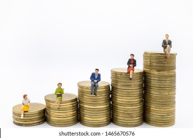 Succession, Business, Money, Security and Saving Concept. Close up of group of businessman and woman miniature figures sitting on top of stack of gold coins on white background and copy space.