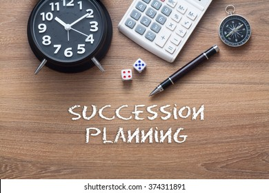 Succession planning written on wooden table with clock,dice,calculator pen and compass
