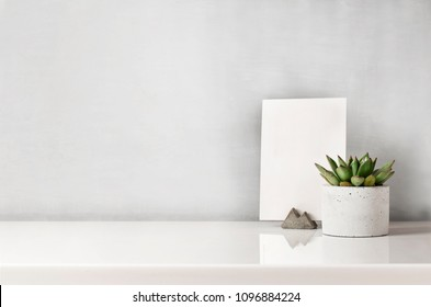 Succulent in a concrete pot on a white bedside table
