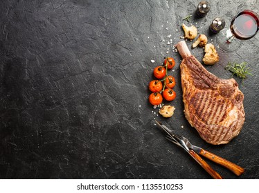 Succulent grilled tomahawk beef steak on the bone with seasonings, fresh rosemary and grilled vegetables on a black background, top view