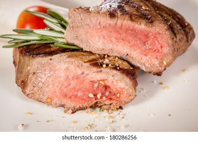Succulent medium rare beef steak sliced through to display the tender red flesh and seasoned with spices and fresh rosemary, close up view