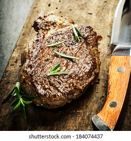 Succulent portion of grilled beef steak garnished with fresh rosemary on a rustic wooden chopping board with a sharp steak knife for a gourmet meal