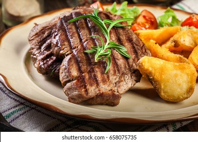 Succulent portions of grilled fillet mignon served with baked potatoes on a plate